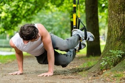 Junger Mann trainiert mit Schlingentrainer