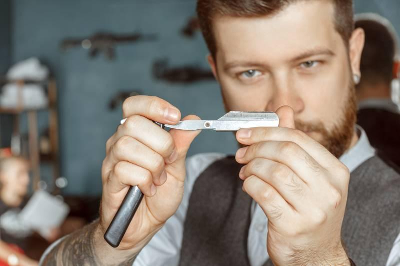 Mann prüft Rasiermesser