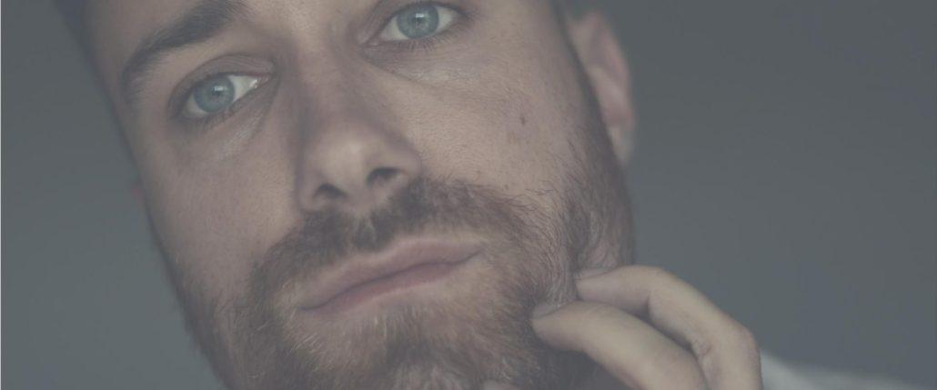Mann kratzt sich am Bart