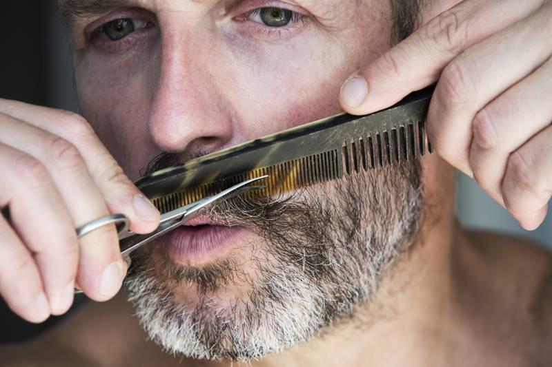 Mann trimmt bart gegen Pieksen