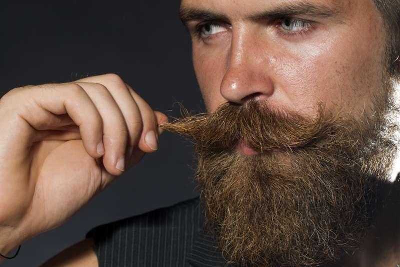 Mann zwirbelt Schnurrbart